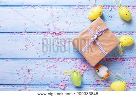 Easter postcard. Box with present bright Easter eggs on blue wooden background. Selective focus. Place for text.