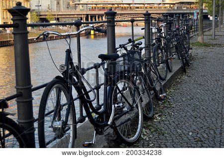 Bicycle Parking At People Stop And Lock Bike At Riverside Of Spree River At Berlin City