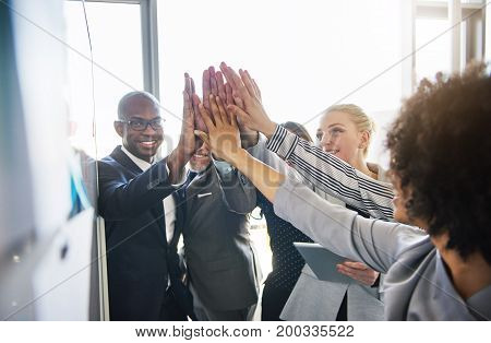 Smilling Colleagues High Fiving Each Other In A Modern Office