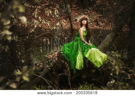 the girl in the woods with a toy in green dress sitting