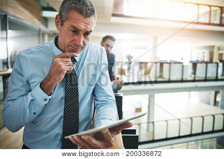 Thoughtful confident adult businessman standing with tablet in office.