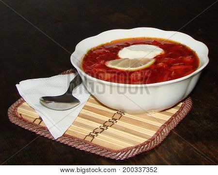 Russian borsch soup in a plate on a wooden table