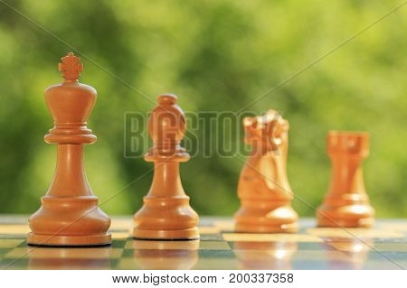 White chess figures on a  wooden chessboard