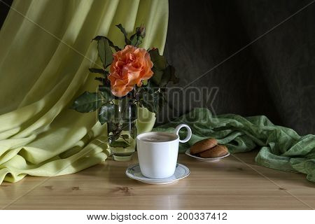 Morning cappuccino and vase of shrub roses in orange on the table close-up