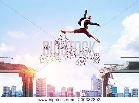 Business woman jumping over gap with gear mechanism in concrete bridge as symbol of overcoming challenges. Cityscape and sunlight on background. 3D rendering.
