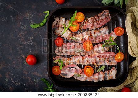 Fried Bacon And Tomatoes In Pan On A Dark Background. Flat Lay. Top View