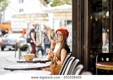 Young stylish woman in red beret smoking a cigarette sitting outdoors at the french cafe