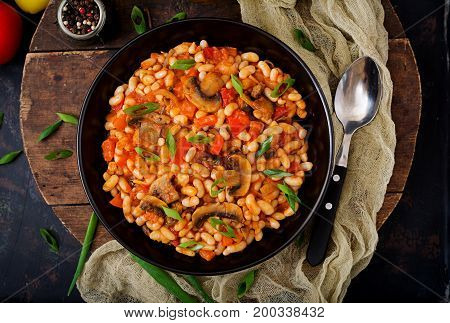 Stewed White Beans With Mushrooms And Tomatoes With Spicy Sauce In A Black Bowl. Top View. Flat Lay