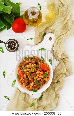 Stewed White Beans With Mushrooms And Tomatoes With Spicy Sauce In A White Bowl. Top View. Flat Lay