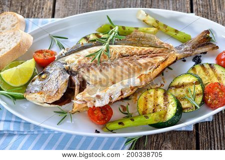 Grilled gilthead seabream with mixed rosemary vegetables served on an oval white fish plate