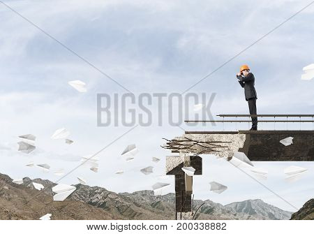 Young engineer in suit and helmet looking in binoculars while standing among flying paper planes on broken bridge with skyscape on background. 3D rendering.
