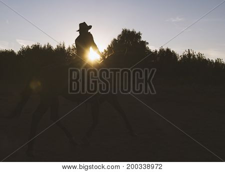 Silhouette of a woman in cowboy hat riding a horse - sunset view