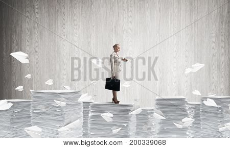 Confident business woman in suit standing among flying paper planes with grey wall on background. Mixed media.