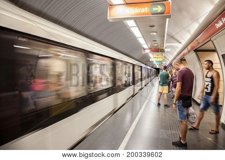 BUDAPEST HUNGARY - AUGUST 12 2017: Metro entering a station of Budapest metro with people waiting in front