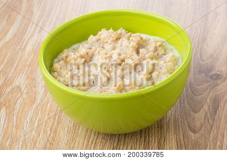Porridge From Oat Flakes With Milk In Green Bowl
