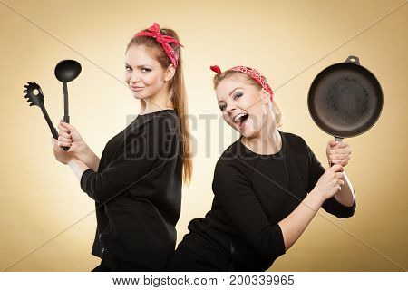 Joy and fun during food preparation. Two blonde smiling women in retro style having fun in kitchen. Playful girls with accessories of cooking.