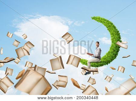Young man on green moon in blue sky with red book in hands