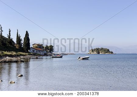 Morning at sea. View of the sea, boats and a small islet in the distance