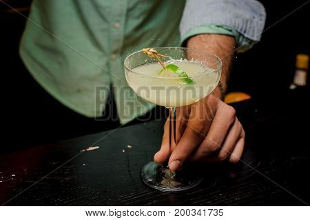 Bartender making cocktail with lime close up