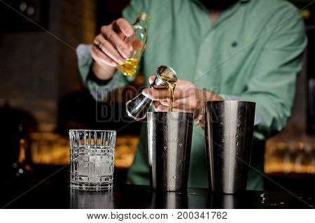 The bartender no face pours alcohol in a bar. Two shakers a bottle a jiger and a glass with ice