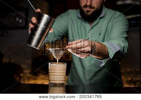 A professional bartender pours alcohol from the shaker. The process of cooking New York sour cocktail