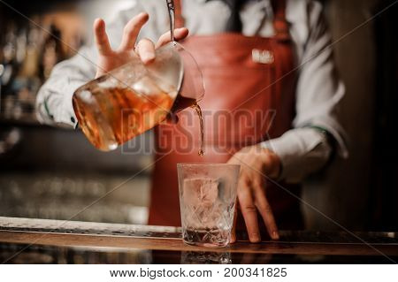Barman's hands in bar interior making alcohol cocktail. Professional bartender pours a drink with a strainer