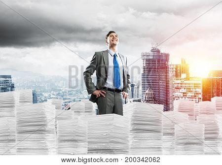 Young confident businessman in suit standing on pile of documents with cityscape and sunlight on background. Mixed media.
