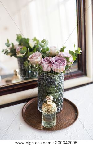 Pastel purple, mauve color fresh summer roses in vase and perfume by the mirror closeup, vintage style