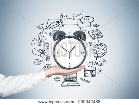 Close up of a hand of an unrecognizable businessman holding an alarm clock with a time management sketch around it near a gray wall.