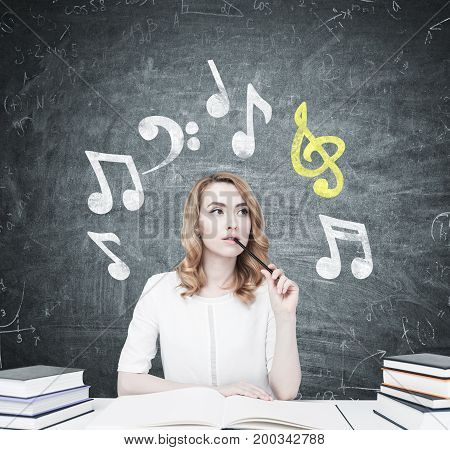 Beautiful young woman is sitting at a table with piles of book on it. The one in front of her is open. She is thinking and biting a pencil. Blackboard with music notes on it