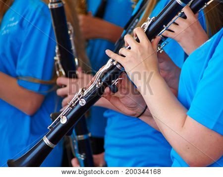 Young woman musician playing clarinet as part of a big orchestra