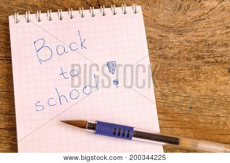 Open white notepad with inscription BACK TO SCHOOL with helium pen on the wooden table
