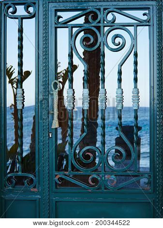 Old vintage Spanish style decorative wrought iron door with the ocean reflected on the glass