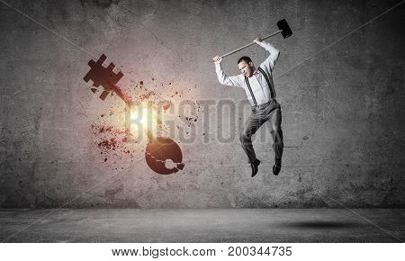 Determined businessman in empty interior breaking with hammer stone key figure