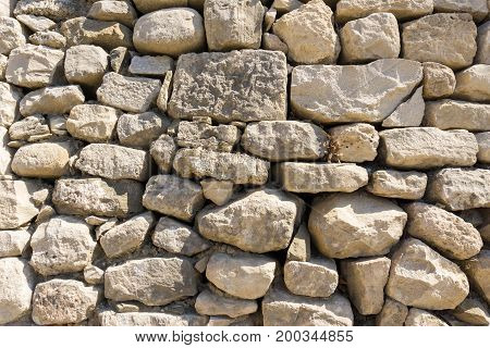Close-up of a white Stone Wall in Sunlight. View on different stacked Stones. Natural Background.