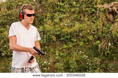 Blonde Caucasian Handsome Guy With Gun Glock Pistol Changing Magazine With Bullets In The Firing Act
