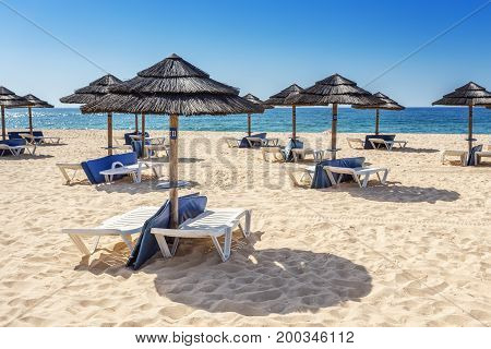 Umbrellas and sunbeds on the southern beach of the Algarve. In Portugal.