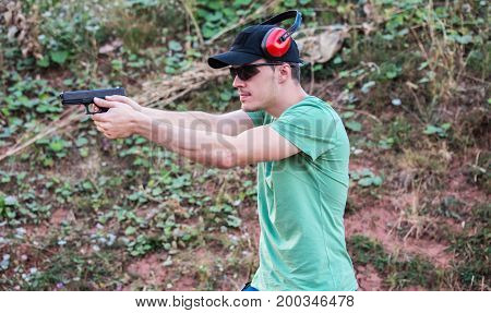 Young And Handsome Policeman Special Force Muscle Training With Pistol And Protective Gear Aiming To