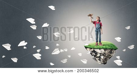 Cute kid girl standing on flying island throwing retro plane