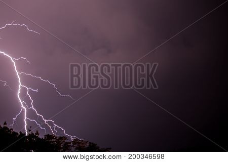 Lighting in the night striking at the ground with sheer force in the storm and clouds in the sky