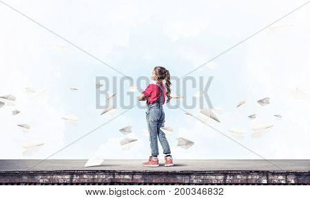 Cute kid girl standing on building roof and paper planes flying around