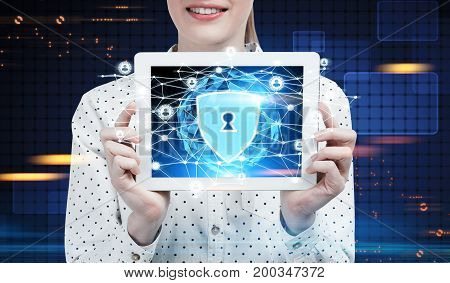 Close up of a businesswoman wearing a polka shirt holding a tablet computer and showing it to the viewer. There is an internet security sketch on it. Dark blue futuristic background HUD. Toned image