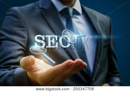 Businessman Showing Seo On A Blue Background.