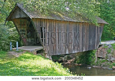 a small restored covered bridge spans a small stream