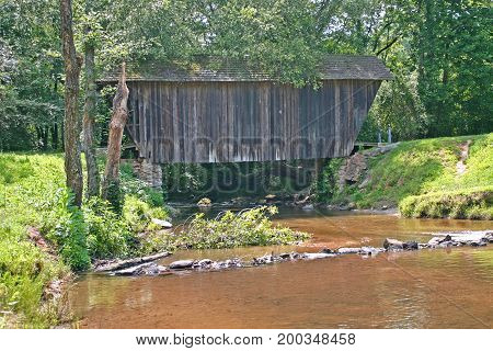 copper-colored water flows beneath a small covered bridge