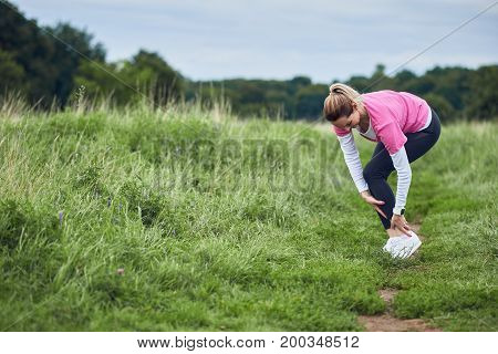 An exercising woman in fit wear while running outdoors stop to clutch an injured ankle.