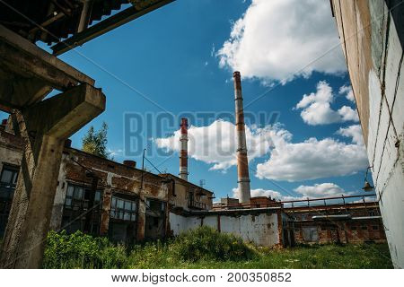 Industrial background, factory with pipes at blue sky background