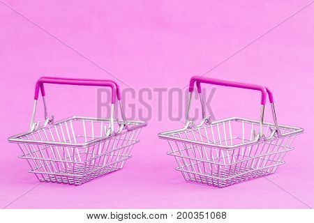Miniature shopping baskets on a purple background