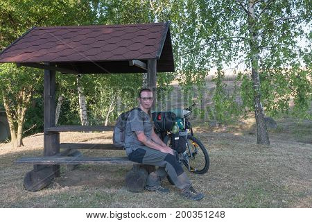 Biker sitting on a bench under gazepo. Camping equipments is mounted on the bike.