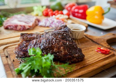 Thick juicy portions of grilled roasted meat on a wooden Board with vegetables
